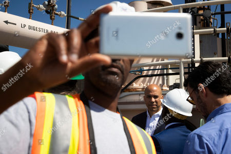 A worker in foreground takes a selfie with Democratic presidential candidate Sen. Cory Booker in the background during Booker's visit to the Hyperion Water Reclamation Plant, in the Playa del Rey section of Los Angeles