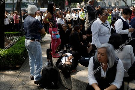 A woman who was overcome after an earthquake swayed buildings lies on a bench where she gets medical attention amidst people evacuated from a federal building on Paseo de la Reforma street in Mexico City, . A magnitude 5.4 earthquake in southern Mexico caused tall buildings to sway in the Mexican capital Monday, prompting hundreds of office workers to briefly evacuate along the central avenue