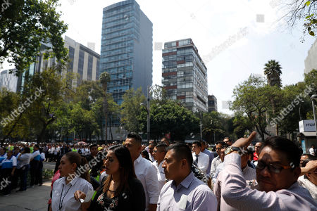 Workers evacuated from a federal building after an earthquake wait on a sidewalk of Paseo de la Reforma street in Mexico City, . A magnitude 5.4 earthquake in southern Mexico caused tall buildings to sway in the Mexican capital Monday, prompting hundreds of office workers to briefly evacuate along the central avenue