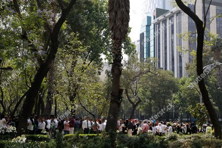 Workers evacuated from a federal building after an earthquake wait on the sidewalk of Paseo de la Reforma street in Mexico City, . A magnitude 5.4 earthquake in southern Mexico caused tall buildings to sway in the Mexican capital Monday, prompting hundreds of office workers to briefly evacuate along the central avenue