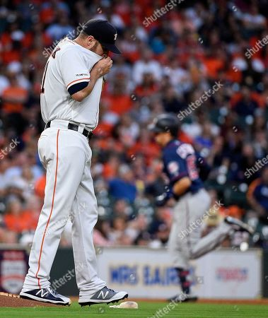 Stock Photo of Houston Astros starting pitcher Brad Peacock, left, walks off the mound as Minnesota Twins' Jason Castro, back right, rounds the bases after hitting a solo home run during the second inning of a baseball game, in Houston