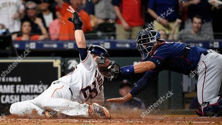 Houston Astros' Josh Reddick, left, is tagged out at home by Minnesota Twins catcher Jason Castro during the fourth inning of a baseball game, in Houston