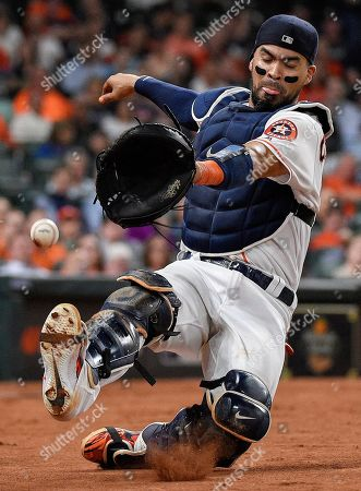 Houston Astros catcher Robinson Chirinos misses the foul ball of Minnesota Twins' Jonathan Schoop during the sixth inning of a baseball game, in Houston