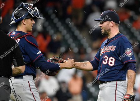 Stock Picture of Minnesota Twins relief pitcher Blake Parker (38) shakes hands with catcher Jason Castro after their victory over the Houston Astros in a baseball game, in Houston