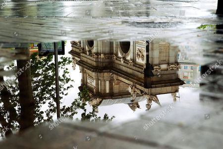 The Puerta de Alcala (Alcala Gate) is reflected in a puddle on a rainy day in Madrid, Spain, 23 April 2019. Spanish State Weather Agency Aemet has forecasted rainy weather for northern half of the country due to a North Atlantic depression.