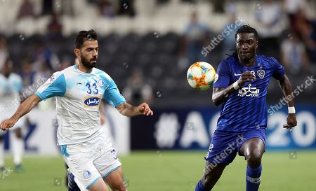 Stock Photo of Bafetibi Gomis (R) of Al Hilal FC in action against Pejman Montazeri of Esteghlal F.C. during the AFC Champions League group C soccer match between Saudi Arabia's club Al Hilal FC and Iran's club Esteghlal F.C. in Abu Dhabi, United Arab Emirates, 23 April 2019.
