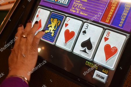 Stock Photo of A player swipes the screen on a video poker machine at the Monte Bar and Casino in Billings, Montana, . Almost a year after the U.S. Supreme Court ended Nevada's monopoly on sports betting, Montana, Iowa and Indiana are poised to legalize sports betting