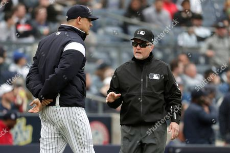 New York Yankees manager Aaron Boone, left, talks with crew chief Jerry Meals during the third inning of a baseball game against the Kansas City Royals, in New York. Meals ruled a fan reached over the wall and interfered as Royals left fielder Alex Gordon went up to make the catch on a ball hit by Yankees' Gleyber Torres. Boone was ejected