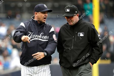 New York Yankees manager Aaron Boone, left, talks with first base umpire Ron Kulpa during the third inning of a baseball game against the Kansas City Royals, in New York. Crew chief Jerry Meals ruled a fan reached over the wall and interfered as Royals left fielder Alex Gordon went up to make the catch on a ball hit by Yankees' Gleyber Torres. Boone was ejected