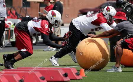 Arizona Cardinals linemen Darius Philon, left, and Corey Peters run drills during an organized NFL team activity, in Tempe, Ariz