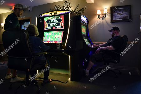 Stock Image of Patrons are seen playing video poker machines at the Palm Grand Casino in Billings, Mont., . Wieland says he's likely to try sports betting as Montana is poised to legalize it