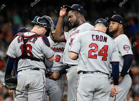 Minnesota Twins starting pitcher Michael Pineda, center, and teammates gather at the mound with pitching coach Wes Johnson, far left, during the fifth inning of a baseball game against the Houston Astros, in Houston