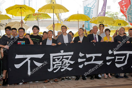 """Eason Chung, Raphael Wong, Tommy Cheung, Lee Wing-tat, Chan Kin-man, Benny Tai, Chu Yiu-ming, Tanya Chan, Shiu Ka-chun. Occupy Central leaders, from left, Eason Chung, Raphael Wong, Tommy Cheung, Lee Wing-tat, Chan Kin-man, Benny Tai, Chu Yiu-ming, Tanya Chan and Shiu Ka-chun holds a banner before entering a court in Hong Kong, . The court is preparing to sentence Tuesday nine leaders of massive 2014 pro-democracy protests convicted last month of public nuisance offenses. The sentences to be handed down Wednesday are seen as an effort by the government of the semi-autonomous Chinese territory to draw a line under the protests. The banner partially seen reads: """"""""The flow of the river is never changed"""