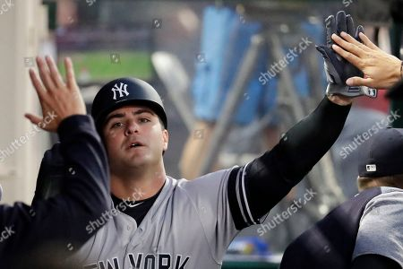 New York Yankees' Mike Ford celebrates in the dugout after scoring on a ball hit by Tyler Wade during the third inning of a baseball game against the Los Angeles Angels in Anaheim, Calif