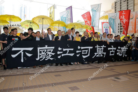 """Occupy Central leaders, from left, Eason Chung, Raphael Wong, Tommy Cheung, Lee Wing-tat, Chan Kin-man, Benny Tai, Chu Yiu-ming, Tanya Chan, Shiu Ka-chun and their supporters hold banner reading """"The flow of the river is never changed,"""" before entering a court in Hong Kong, . The court is preparing to sentence Tuesday nine leaders of massive 2014 pro-democracy protests convicted last month of public nuisance offenses. The sentences to be handed down Wednesday are seen as an effort by the government of the semi-autonomous Chinese territory to draw a line under the protests"""