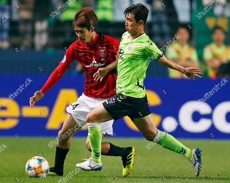 Koya Yuruki (L) of Urawa Red Diamonds in action against Lee Seung-gi (C) of Jeonbuk Hyundai Motors FC during the AFC Champions League group G soccer match between Urawa Red Diamonds and Jeonbuk Hyundai Motors FC at the Jeonju World Cup Stadium in Jeonju, South Korea, 24 April 2019.
