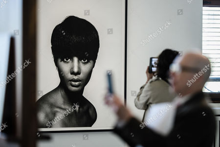 Visitors take photos in front of a photo by Moneta Sleet Jr. (1965) during a press preview of the exhibition 'The Black Image Corporation' by Theaster Gates at the Martin Gropius Bau museum in Berlin, Germany, 24 April 2019. Concept artist Theaster Gates presents the work of photographers Moneta Sleet Jr. and Isaac Sutton and the Afroamerican culture magazines Ebony and Jet. The exhibition runs from 24 April to 28 July 2019 at the Martin Gropius Bau museum in Berlin.