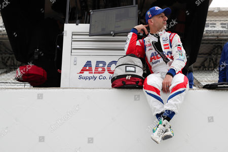 IndyCar driver Tony Kanaan, of Brazil, sits on the pit wall during auto racing testing at the Indianapolis Motor Speedway in Indianapolis