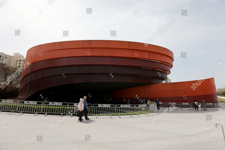 Stock Picture of People walk near the Holon Design Museum, in the city of Holon, Israel, 24 April 2019. The museum designed by Israeli architect and industrial designer Ron Arad was first opened on 03 March 2010.