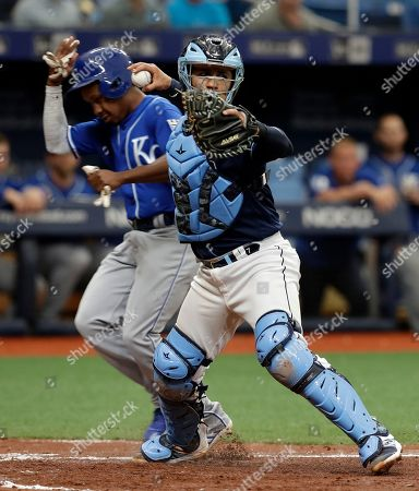 Terrance Gore, Michael Perez. Tampa Bay Rays catcher Michael Perez, right, forces Kansas City Royals' Terrance Gore at home plate and throws the ball to first in time to turn a double play on Adalberto Mondesi during the fourth inning of a baseball game, in St. Petersburg, Fla