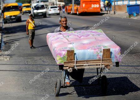 A man carries a bed in a wheelbarrow on one of the streets of Havana, Cuba, 24 April 2019.
