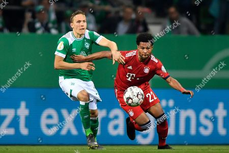 Stock Image of Bayern's Serge Gnabry, right, and Bremen's Ludwig Augustinsson vie for the ball during the German soccer cup, DFB Pokal, semifinal match between Werder Bremen and Bayern Munich at the Weser stadium in Bremen, Germany