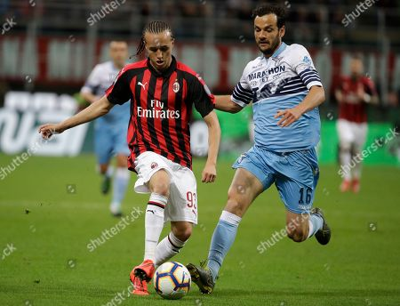 AC Milan's Diego Laxalt, left, and Lazio's Marco Parolo fight for the ball during the Italian Cup, second leg semifinal soccer match between AC Milan and Lazio, at the San Siro stadium, in Milan, Italy