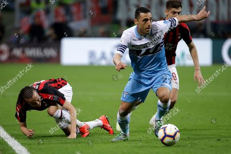 Lazio's Romulo, right, keeps the ball as AC Milan's Diego Laxalt falls during the Italian Cup, second leg semifinal soccer match between AC Milan and Lazio, at the San Siro stadium, in Milan, Italy