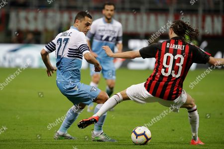 Lazio's Romulo, left, passes the ball as AC Milan's Diego Laxalt defends during the Italian Cup, second leg semifinal soccer match between AC Milan and Lazio, at the San Siro stadium, in Milan, Italy