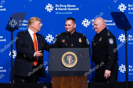 President Donald Trump, left, introduces Customs and Border Patrol officers Long and Noble to speak during the RX Drug Abuse & Heroin Summit, in Atlanta. The President was on hand to provide an update on the nation's opioid epidemic to elected leaders and health and law enforcement officials, about what he has called a national health emergency due to an estimated 2 million people whom are addicted to the drugs