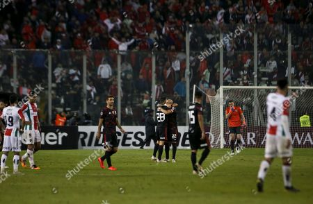 Lucas Martinez, center left, and Javier Pinola of Argentina's River Plate, hug at the end of their Copa Libertadores soccer match against Chile's Palestino in Santiago, Chile, . River Plate won 2-0