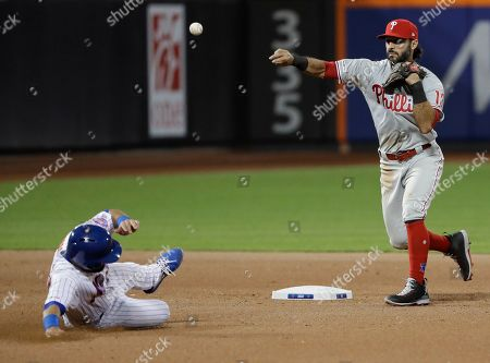 Philadelphia Phillies' Sean Rodriguez, right, throws out New York Mets' Jeff McNeil at first base after forcing out Luis Guillorme, left, during the seventh inning of a baseball game, in New York
