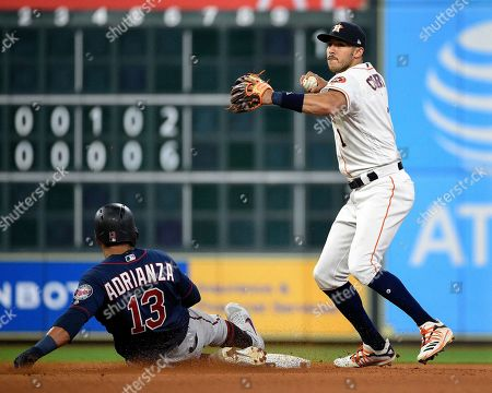 Houston Astros shortstop Carlos Correa, right, attempts a double play over Minnesota Twins' Ehire Adrianza during the eighth inning of a baseball game, in Houston. Jason Castro was safe at first
