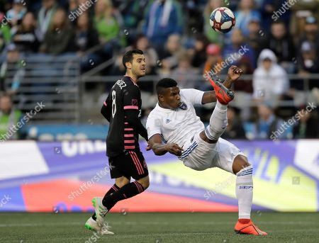 Stock Photo of San Jose Earthquakes defender Harold Cummings, right, makes a defensive bicycle kick to clear the ball away from Seattle Sounders midfielder Victor Rodriguez, left, during the first half of an MLS soccer match, in Seattle