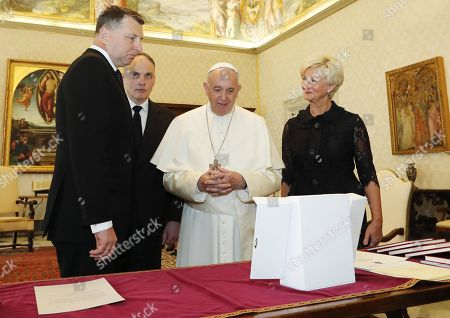 Latvian President Raimonds Vejonis (L) and his wife Iveta Vejone (R) exchange gifts with Pope Francis (C) at the Vatican