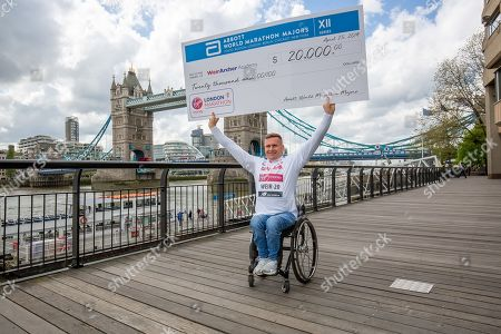 David Weir holds the $20.000 dollars cheque of the Abbot World Majors Charity Program to represent 20 years of London Marathon Competition