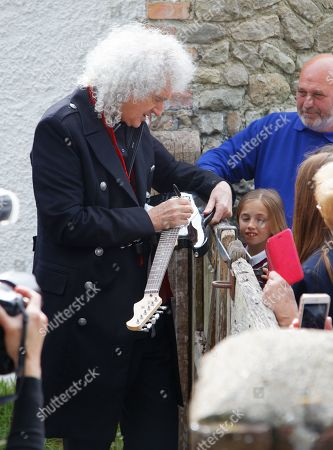 Brian May signs a guitar for a fan at Sir Patrick's former home