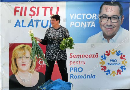 A Romanian woman street vendor sells fresh cooking herbs in front of a banner campaigning for European parliamentary elections on behalf of Pro Romanian Party candidates, in Bucharest, Romania, 25 April 2019. European Union parliamentary elections will take place from 23 until 26 May 2019. The banner depicts Romania's former Prime Minister Victor Ponta (R) and European Commissioner for Regional Policy Corina Cretu (down-L), and reads:' Be with us: Sign for Pro Romania'