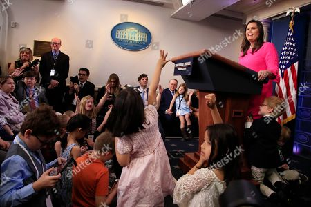 Stock Picture of Huck Sanders, George Sanders, Sarah Huckabee Sanders. White House press secretary Sarah Huckabee Sanders with her children Huck Sanders, with eye glasses, and George Sanders, conducts a briefing for children of journalists and White House staff in the Brady press briefing room at the White House in Washington, to commemorate Take Our Daughters and Sons to Work Day