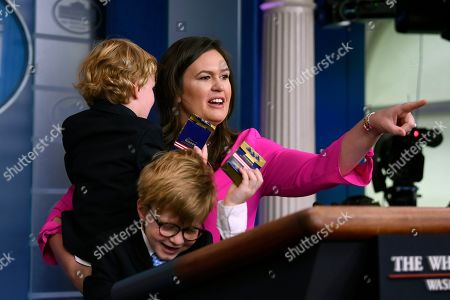 Stock Photo of Sarah Sanders, Huck Sanders, George Sanders. White House press secretary Sarah Sanders, holding her son George and standing next to her son Huck, speaks during a briefing at the White House in Washington, . Children of journalists and White House staff were invited to attend the briefing and ask Sanders questions