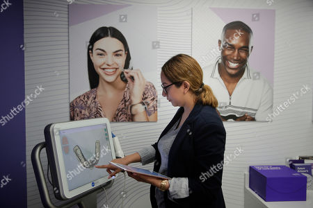 Dental assistant Jessica Buendia looks at a scanned image of patient's teeth in SmileDirectClub's SmileShop located inside a CVS store, in Downey, Calif. CVS Health is venturing into dental care with plans to offer the relatively new teeth-straightening service