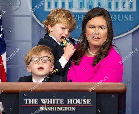 """White House Press Secretary Sarah Huckabee Sanders, with her sons, Huck Sanders, lower left, and George Sanders, center, takes questions from children of White House staff and journalists in observance of """"Take Our Daughters and Sons to Work Day"""" in the Brady Press Briefing Room of the White House"""