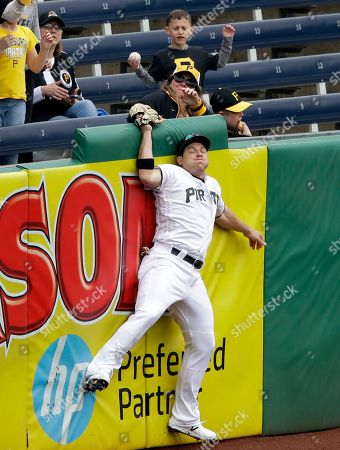Pittsburgh Pirates left fielder JB Shuck hits the outfield wall after making the catch on a hit by Arizona Diamondbacks' Eduardo Escobar in the seventh inning of a baseball game in Pittsburgh