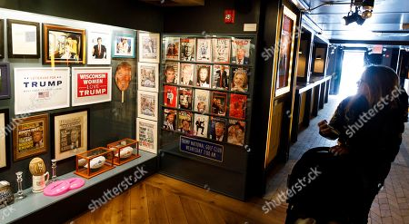 A woman looks at pictures, games, and magazines on display in Andres Serrano's installation 'The Game: All Things Trump', a display of over 1,000 pieces of Donald Trump-related memorabilia and souvenirs collected by Serrano, in New York, New York, USA, 25 April 2019. The items in the installation, which Serrano purchased over the past year at auctions and on eBay, span from Trump's early days in the New York, to his days on television and up to the present day.