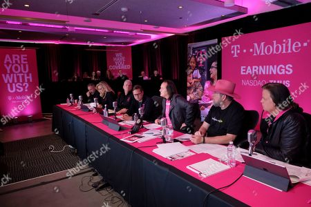 T-Mobile executives, including CEO John Legere, third from right, President Mike Sievert, fourth from right, CFO Braxton Carter, second from right, and Chief Technology Officer Neville Ray, fifth from right, report on another record-breaking quarter during the T-Mobile Q1 2019 Earnings Call, reporting its best ever Q1 financials, from the company's headquarters in Bellevue, Wash