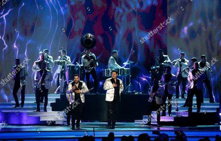 Alan Ramirez, Oswaldo Silvas. Alan Ramirez, left, and Oswaldo Silvas, and Banda Sinaloense MS de Sergio Lizarraga, perform at the Billboard Latin Music Awards, at the Mandalay Bay Events Center in Las Vegas