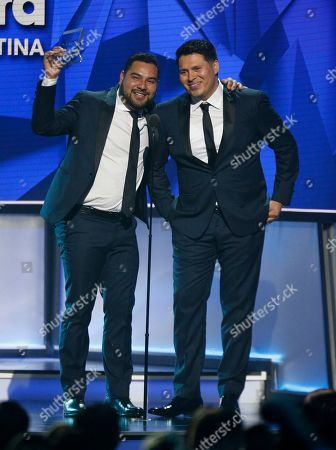 Alan Ramirez, Oswaldo Silvas. Alan Ramirez, left, and Oswaldo Silvas, of Banda Sinaloense MS de Sergio Lizarraga, accept the award for hot latin songs artist of the year, duo or group at the Billboard Latin Music Awards, at the Mandalay Bay Events Center in Las Vegas