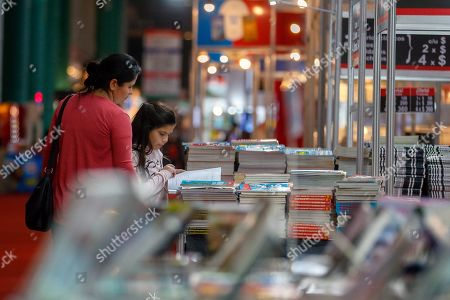 People look at books during the first day of the 45th International Book Fair of Buenos Aires, in Buenos Aires, Argentina, 25 April 2019. The fair, considered the largest in South America, will run until 13 May and will bring together prominent authors such as Arturo Perez-Reverte, Rosa Montero and John Katzenbach. Barcelona, Spain is this year?s guest city of honor.