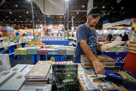 A man places price tags on books for sale during the first day of the 45th International Book Fair of Buenos Aires, in Buenos Aires, Argentina, 25 April 2019. The fair, considered the largest in South America, will run until 13 May and will bring together prominent authors such as Arturo Perez-Reverte, Rosa Montero and John Katzenbach. Barcelona, Spain is this year?s guest city of honor.