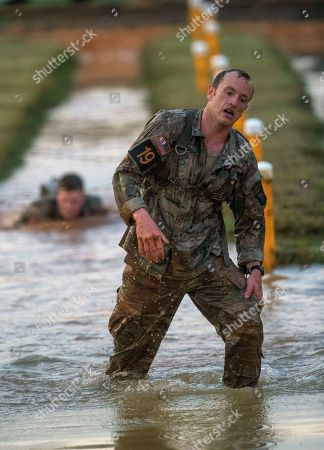 U.S. Army Capt. Michael Rose, of the 101th Airborne, emerges from muddy water after crawling under barbed wire on the Melvesti course during the Best Ranger, at Fort Benning, Ga. Rose and his partner Capt. John Bergman, background, won the event